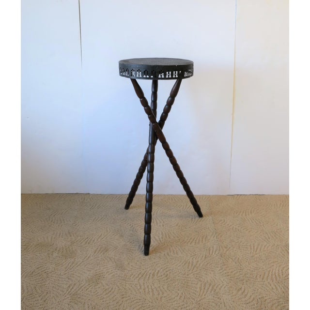 A great early 20th century wood and black metal tripod side table. Table has a black hammered metal top with decorative...