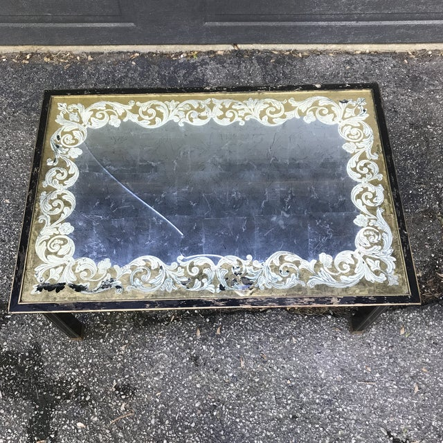 Black table with gold trim. Underside of glass top has gold and silver foil in an art nouveau style. Take notice of the...