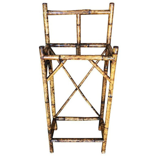 Antique tiger bamboo umbrella stand with back rail, featuring two slots for storing umbrellas and canes. Refinished to new...