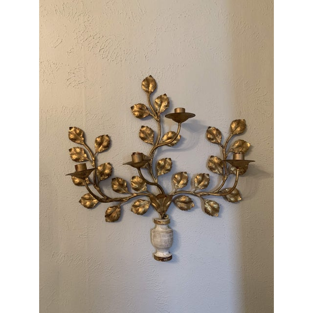 Lovely Gold vintage Italian gilt metal and wood four-light wall sconce from the 1950's. This piece features a carved and...