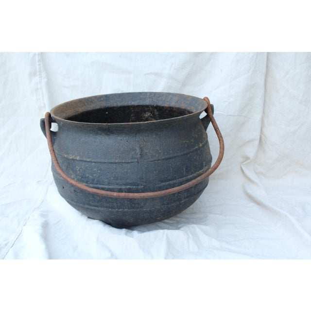 Cast iron cauldron, ribbed, with handle. Made circa late 19th century.