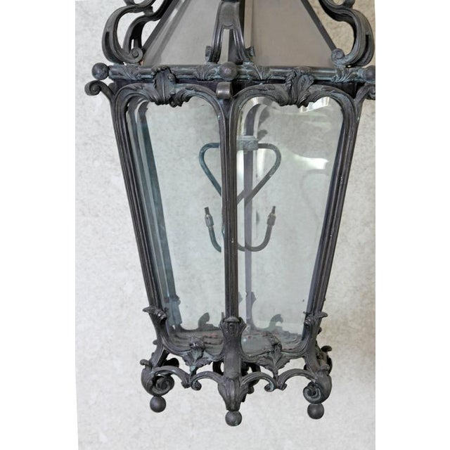 A large pair of Louis XV style bronze wall hanging gas lanterns with six (6) sided glass panels. Each lantern is suspended...