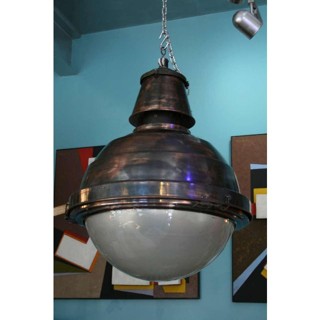 Large-scale hanging pendant, half copper, half glass, with cast iron and bronze detail.