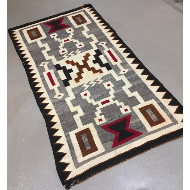 A vintage hand woven Navajo rug measuring 2 feet 8 inches by 4 feet 11 inches. Depicting a Storm Pattern. Circa 1930.