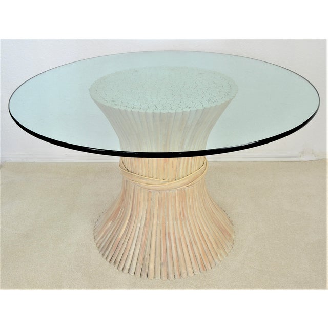 Offering an original vintage McQuire Wheat Sheaf bamboo/rattan dining table with round glass top, circa 1970's. This...