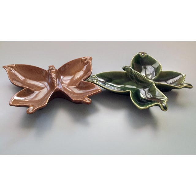 A pristine pair of Van Briggle pottery ashtrays in the form of a butterfly. One is emerald green and the other is a rare...