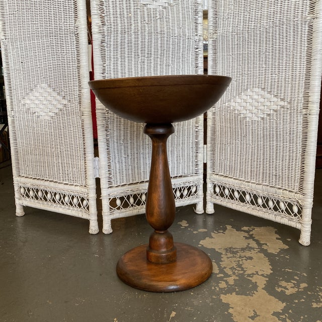 Cool antique wooden bowl on a stand. Great for fruits in the dining room or storing your crafts in the living room.