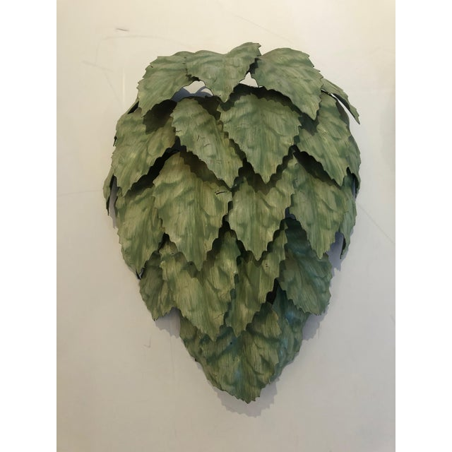 A fabulously whimsical pair of green painted tole sconces having meticulously layered rows of leaves that create...
