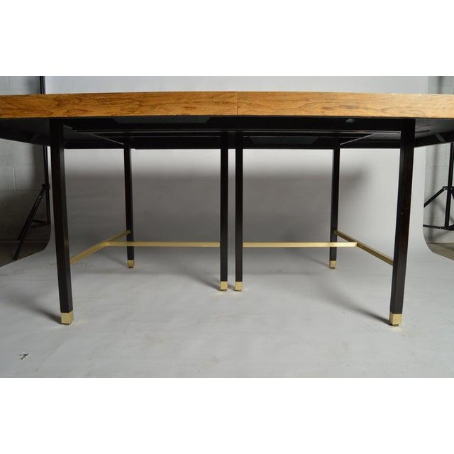 A stunningly elegant expandable dining table in rosewood having mahogany and cast iron legs with brass accents throughout....