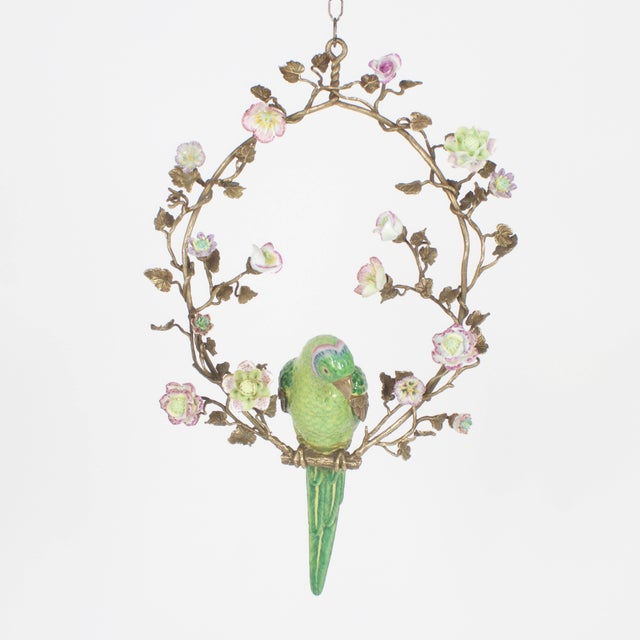 Inspired, opposing pair of French porcelain wall mount parrots perched on a finely crafted brass wreath with porcelain...
