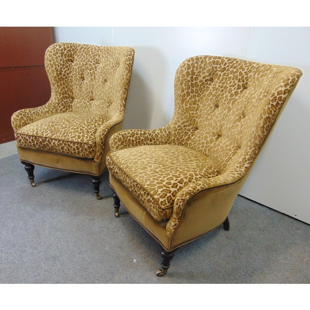 A pair of Hollywood Regency style wing back lounge chairs . Cut velvet leopard print , tufted backs , brown velvet...