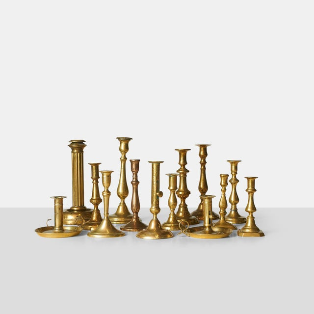 A collection of sixteen brass candle sticks, various sizes and shapes. Various designers and manufacturers, mostly from...