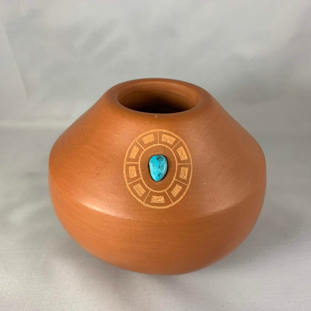 Impeccably crafted clay jar signed by San Ildefonso artist Marie Gonzales Pena. Turquoise gem inlay glows inside circular...