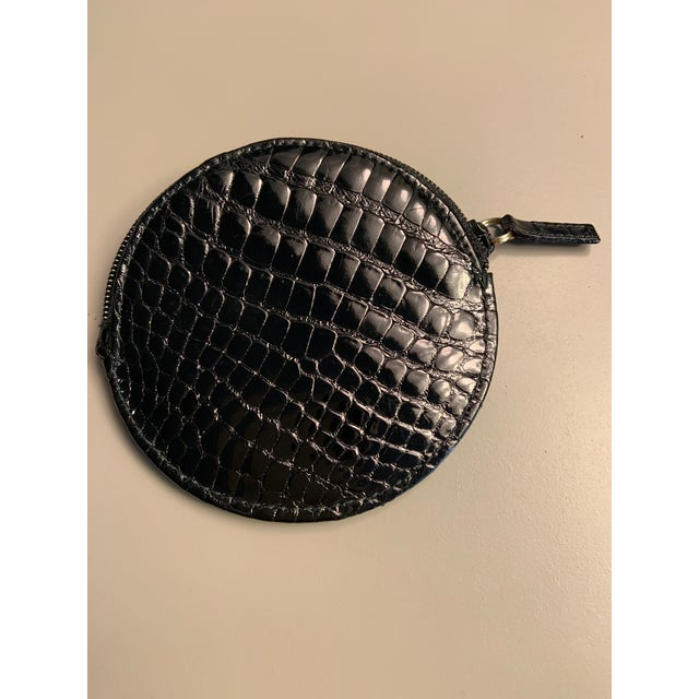 Shiny black alligator on both sides, with a black zipper at the top makes a very elegant coin purse from Gucci. Never...
