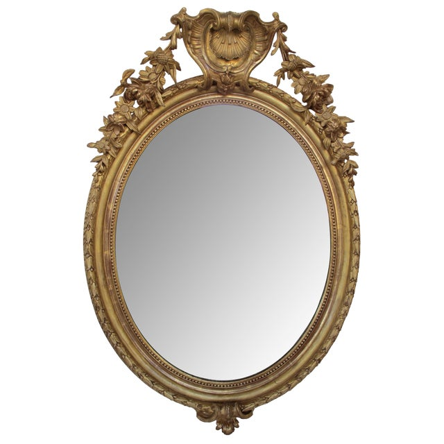 A Finely-Carved French Napoleon III Oval Giltwood Mirror with Shell Crest and Floral Garland For Sale