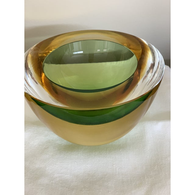 This sophisticated glass bowl in vibrant green and yellow was created by Luigi Onesto (b. 1935 - ) following a 1,000-year-...