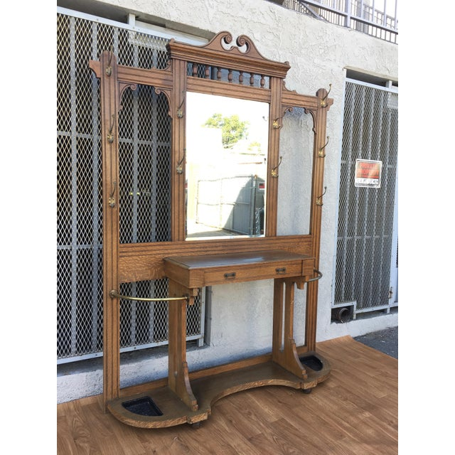 Antique wooden oak hall tree with mirror and drawer, with bronze hangers. Made in the 1940s.