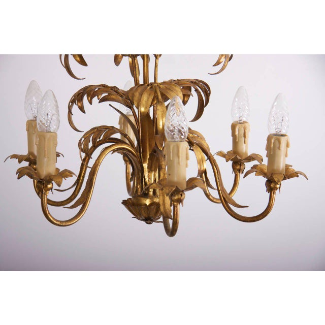 Wonderful gilt metal chandelier with palm tree leaves. The chandelier brings a cozy atmosphere in every room and it is in...