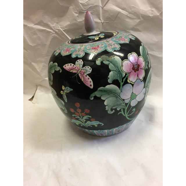 A very beautiful Asian ginger jar decorated with flowers and butterflies over a black background. Fine details.