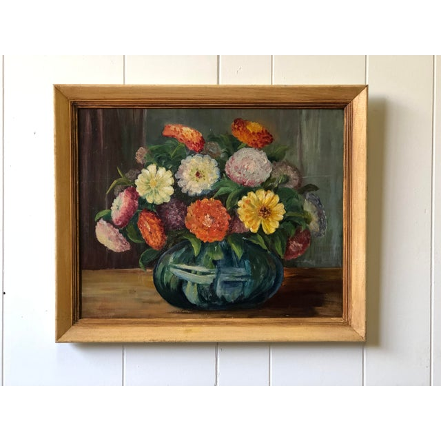 20th Century oil on board still life painting of brightly colored flowers in a round blue glass vase. The painting is held...