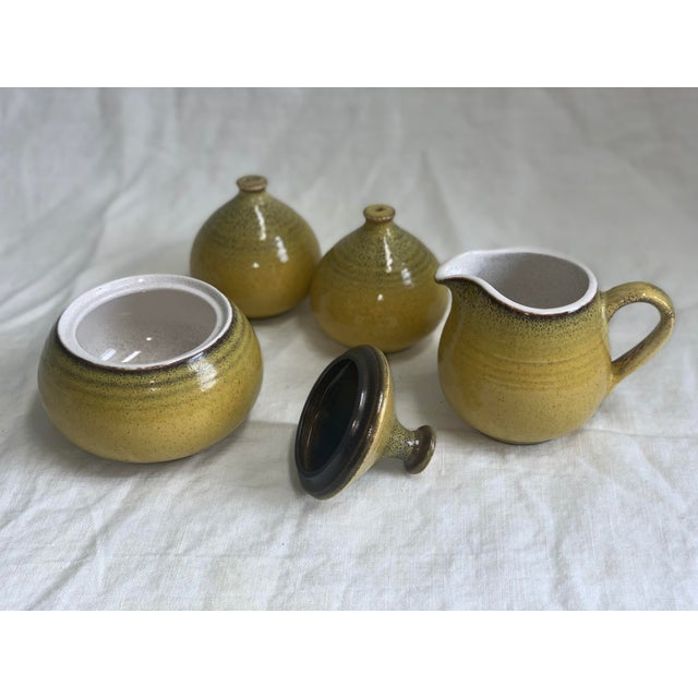 A cheerful yellow stoneware set of salt and pepper shakers, plus tea and coffee a sugar bowl and creamer pitcher. Mint...
