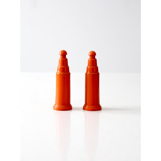 This is a vibrant set of push top vintage salt and pepper shakers. The orange plastic shakers feature a modern silhouette....