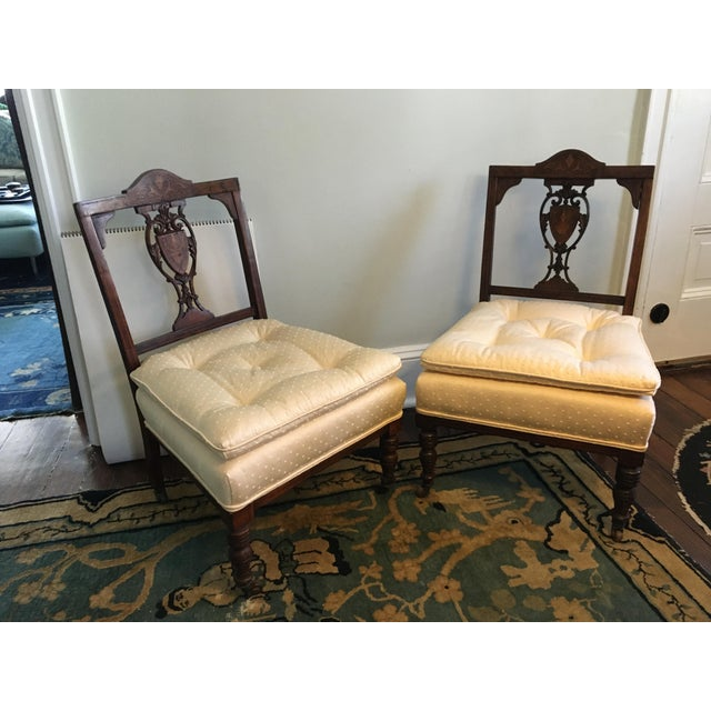 A pair of diminutive 19th century Hepplewhite style accent chairs with intricate carving and marquetry. Beautifully...