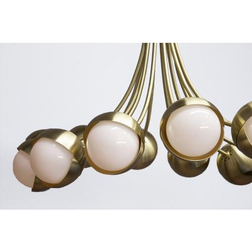 The Benedict Chandelier by Trella is shown in a twelve light configuration in satin brass. The Benedict is available in a...