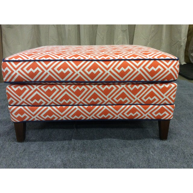 Vintage ottoman is newly upholstered in orange and white cotton fabric with blue pipping. With wooden legs . There is wear...