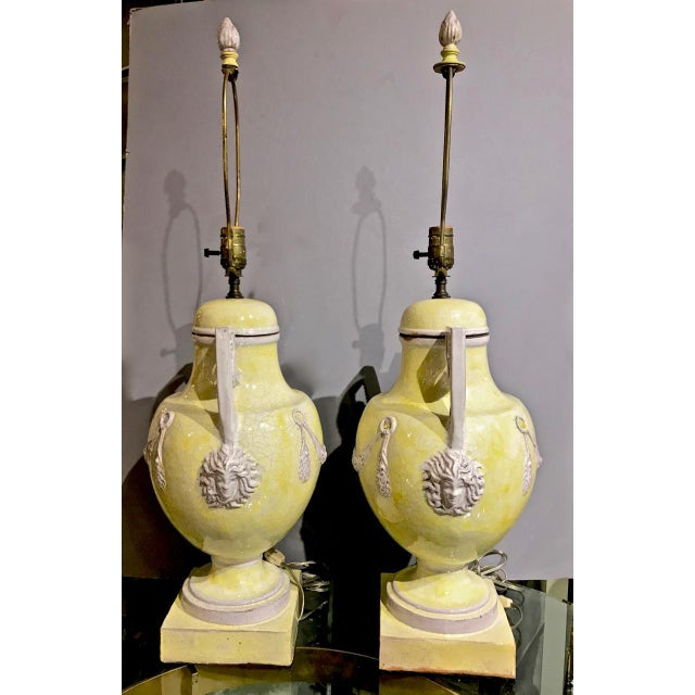 This is an exceptional pair of midcentury glazed terra cotta or Majolica lamps with neoclassical urn-form bases. The...