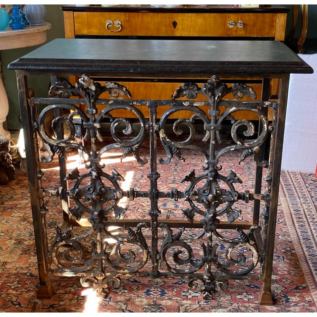 """Iron console with scrolled black iron base with black marble top. Made in the 19th century. 35"""" Wide x 17.5"""" Deep x 34.5""""..."""