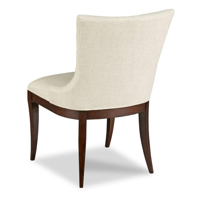 A curved upholstered back wraps around an upholstered seat raised by graceful tapering saber legs. Material: Hardwood Solids.