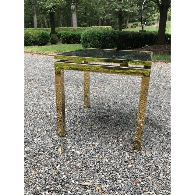 Stunning mid-century Guy Lefevre for Maison Jansen side table in brass and smoked dark glass. Elegant turned in feet;...