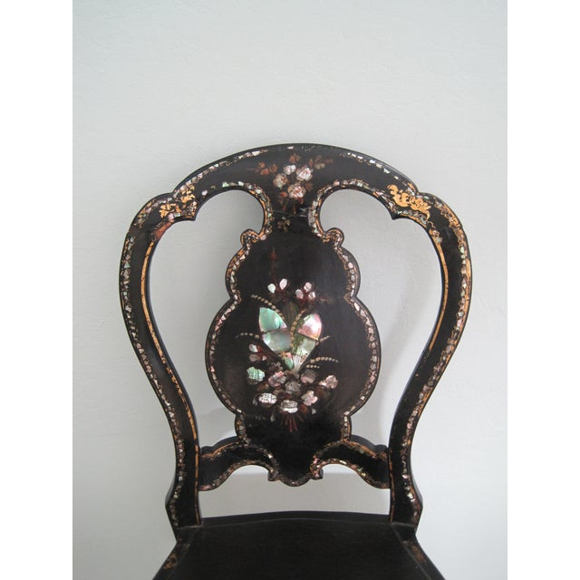 Victorian black lacquer papier mache chair. Mother of Pearl inlay with hand painted flowers and gold highlights. This...