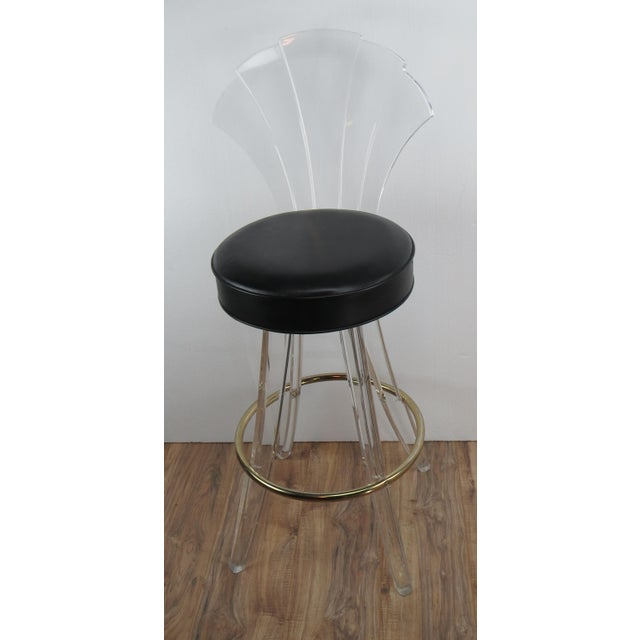 Unique vintage Lucite bar stool with fan back. Black vinyl seat that swivels. Solid Lucite legs and brass ring footrest.