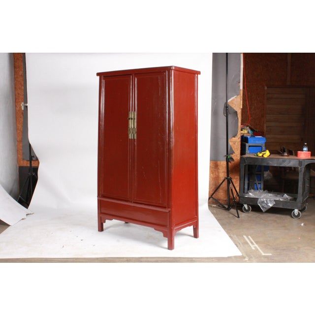 Vintage Ming-Style red laquered wedding cabinet wardrobe featuring simple lines and two doors that open to reveal two...
