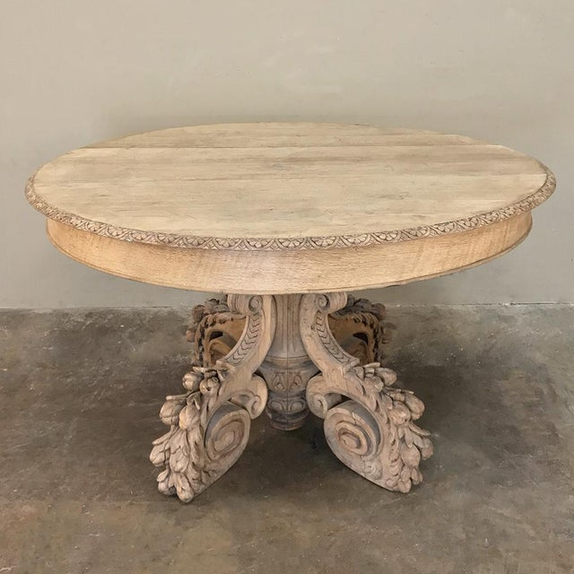 19th Century French Renaissance Stripped Center Table is a marvel to behold, with elaborately sculpted quatrepod scrolled...