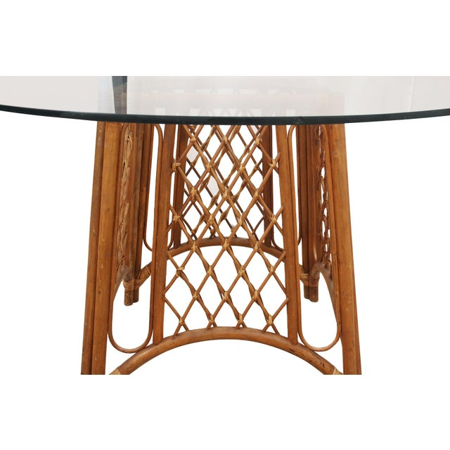 A bamboo and glass pedestal table. The base is made of bamboo with trellis panels on each side secured with rattan. The...