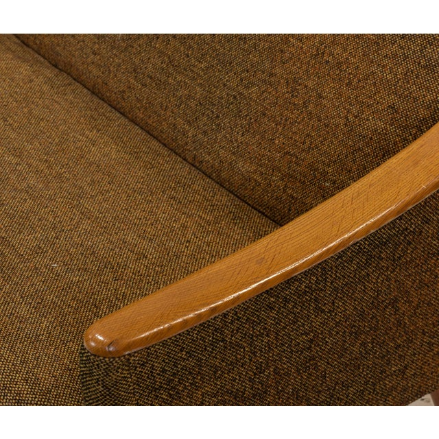 Mid century modern sofa with curved wooden armrests. Upholstered with forest green upholstery.