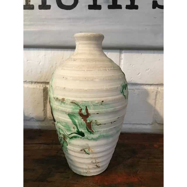 Tourist pottery vase with green and brown accent swirls on white background. Textured ribbed design. This vase is unmarked...
