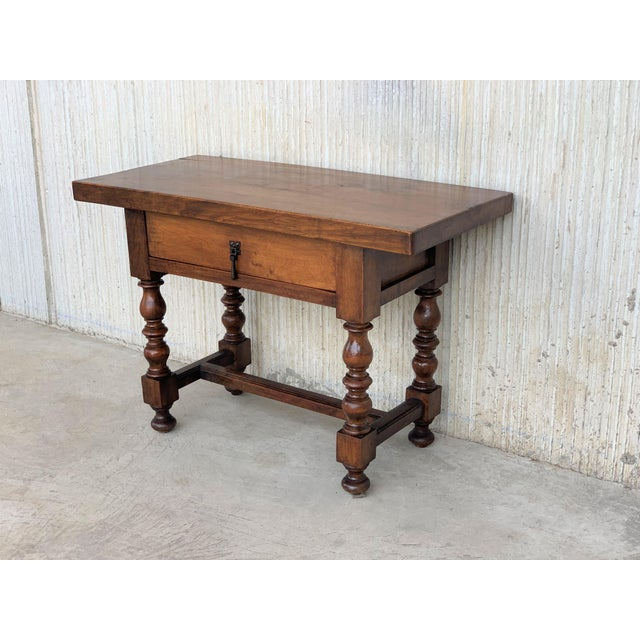 About A Spanish walnut side table with single drawer, scalloped apron and turned legs r from the late 19th century. This...