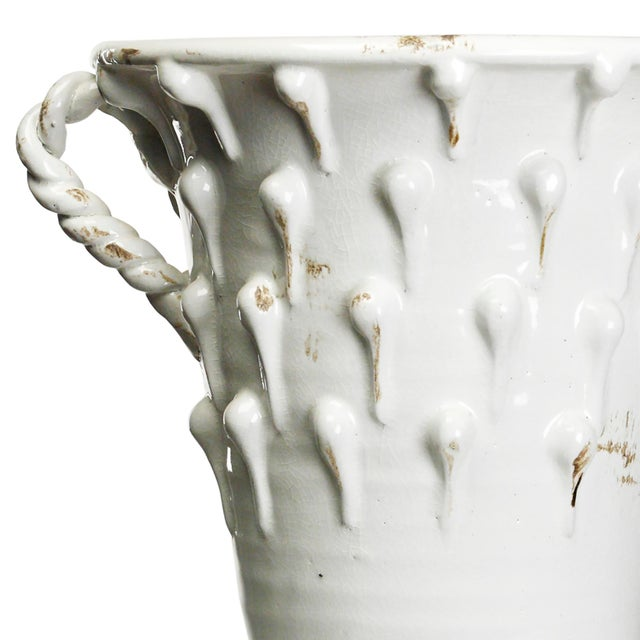 Decorative distressed white pottery with handles.