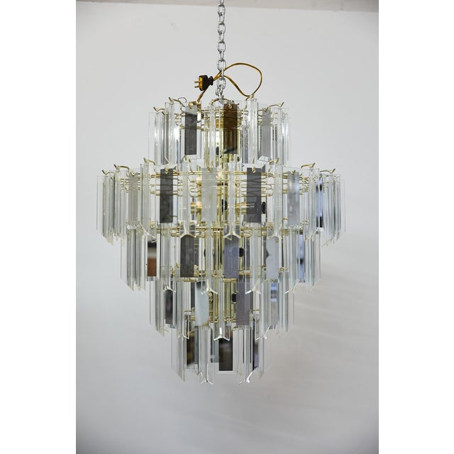 Vintage Italian five-tier waterfall or wedding cake style chandelier having a cylindrical brass frame and fittings. The...
