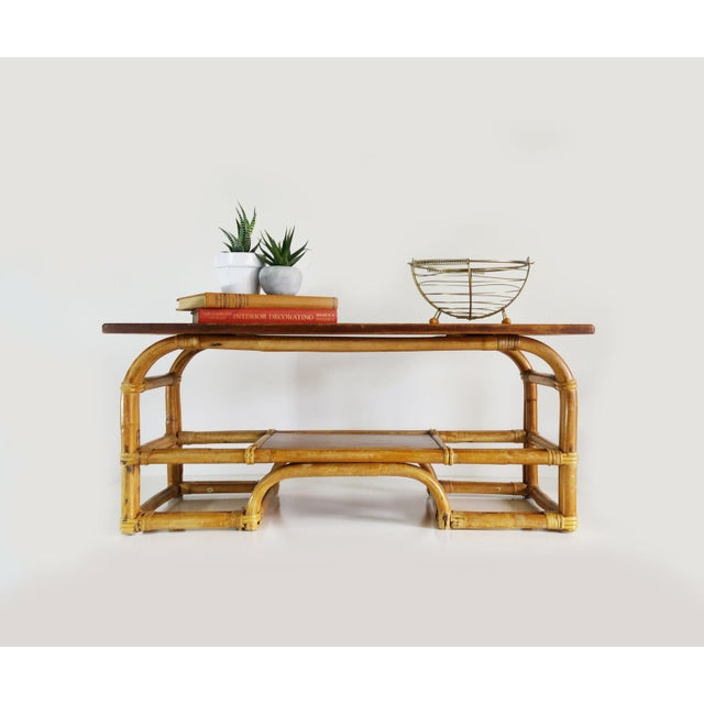 A rectangular bamboo coffee table with wood top and lower shelf on a bent bamboo frame. Top measures 36 inches by 16...