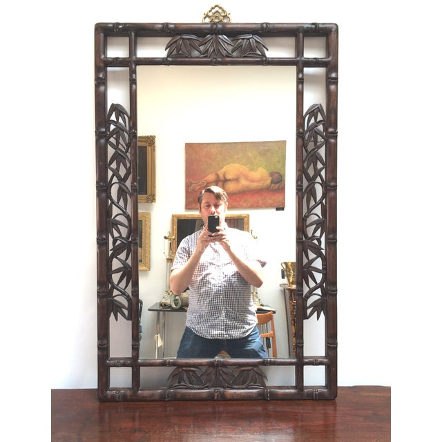 A carved wood mirror featuring faux bamboo stalk frame with inset carved bamboo leaves, c. 1930's. Decorative brass...