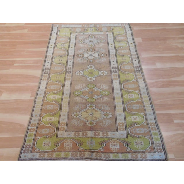 This is an vintage hand knotted rare Turkish rug from the village of Oushak. The rug has a semi geometric pattern with...