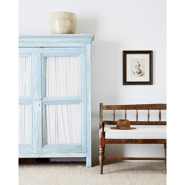 Rustic country French armoire cabinet made in the Provincial style. Features a beautiful French blue painted finish with a...