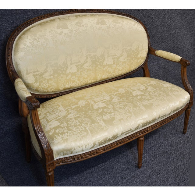 The carved wooden edges frame this Louis XVI style settee, ending on the oval backrest which is crowned with floral...