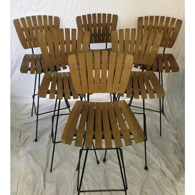 Set of 6 mid-century Arthur Umanoff bar stools. Iconic wood slats with original patina. Slender black iron bases with...