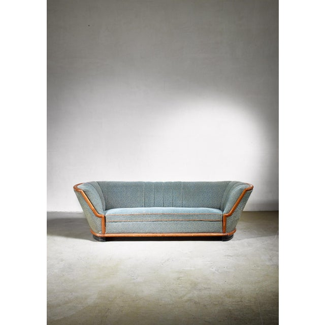 A wonderful tub shaped 1940s three seater sofa from Denmark. The sofa has a mahogany frame with a greyish blue wool...